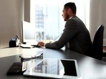 Schattenbild des Geschäftsmannes unter Verwendung des Laptops Stockfotografie