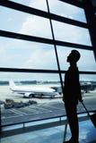 Schattenbild des Geschäftsmannes wartend in den Flughafen und das Fenster heraus schauend Lizenzfreies Stockfoto