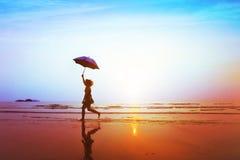 Schattenbild des glücklichen sorglosen Mädchens mit dem Regenschirm, der auf den Strand springt stockbild