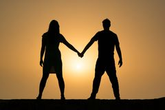Schattenbild des Händchenhaltens eines Paares im Sonnenuntergang Lizenzfreie Stockbilder