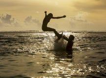 Schattenbild des Herausspringens der jungen Frau von Ozean Stockfotografie