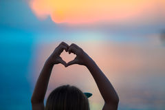 Schattenbild des Herzens gemacht durch Kinderhand bei Sonnenuntergang Lizenzfreies Stockbild