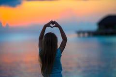 Schattenbild des Herzens gemacht durch Kinderhand bei Sonnenuntergang Lizenzfreie Stockfotografie