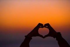 Schattenbild des Herzens stellte Hände bei Sonnenuntergang her Stockfoto