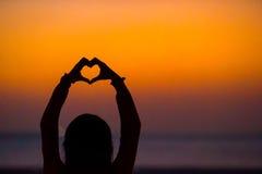 Schattenbild des Herzens stellte Hände bei Sonnenuntergang her Lizenzfreies Stockfoto
