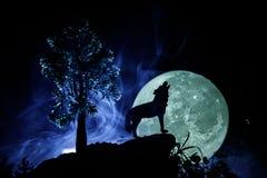 Schattenbild des Heulenwolfs gegen dunklen getonten nebeligen Hintergrund und Vollmond oder Wolf im Schattenbild heulend zum Voll Stockfotos