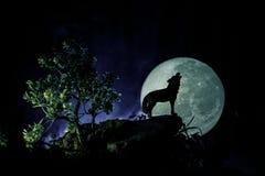 Schattenbild des Heulenwolfs gegen dunklen getonten nebeligen Hintergrund und Vollmond oder Wolf im Schattenbild heulend zum Voll Lizenzfreie Stockfotografie