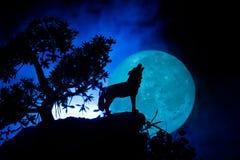 Schattenbild des Heulenwolfs gegen dunklen getonten nebeligen Hintergrund und Vollmond oder Wolf im Schattenbild heulend zum Voll Lizenzfreies Stockfoto