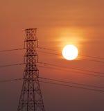 Schattenbild des Hochspannungsstrombeitrags mit Sonnenuntergang backgro Stockfotografie
