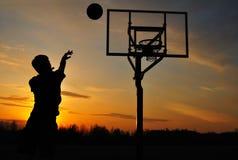 Schattenbild des jugendlich Jungen einen Basketball schießend Lizenzfreie Stockbilder