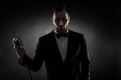 Schattenbild des jungen hübschen Sängers auf schwarzem Hintergrund Lizenzfreies Stockbild