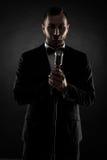 Schattenbild des jungen hübschen Sängers auf schwarzem Hintergrund Lizenzfreie Stockfotos