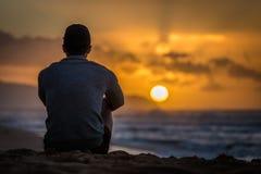 Schattenbild des jungen kaukasischen Mannes, der auf dem Sonnenuntergang-Strand heraus betrachtet Sonnenuntergang über dem Ozean  stockbild