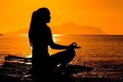 Schattenbild des jungen Mädchens meditierend auf dem Meer Lizenzfreie Stockfotos