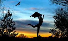 Schattenbild des jungen Mädchens mit Schaltanzen auf blauem und goldenem bewölktem Sonnenuntergang Stockfoto