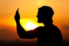 Schattenbild des jungen Mannes, der sein smartpone verwendet Stockbild