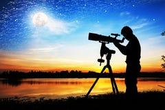 Schattenbild des jungen Mannes schauend durch ein Teleskop Stockbild