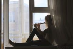 Schattenbild des jungen netten jugendlich Mädchens, das auf der Flöte zu Hause sitzt auf Fensterbrett spielt stockfoto