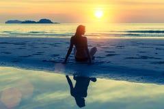 Schattenbild des jungen schönen Mädchens, das auf dem Strand sitzt stockbilder