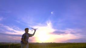 Schattenbild des Jungen seine Flugzeuge gegen Sonnenuntergang laufen lassend stock footage