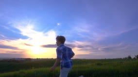 Schattenbild des Jungen seine Flugzeuge gegen Sonnenuntergang startend stock video footage