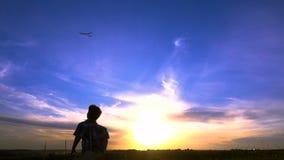 Schattenbild des Jungen seine Flugzeuge gegen Sonnenuntergang startend stock video