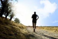Schattenbild des jungen Sportmannes, der auf Landschaft im Cross Country-Training bei Sommersonnenuntergang läuft Stockfotos