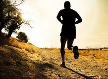 Schattenbild des jungen Sportmannes, der auf Landschaft im Cross Country-Training bei Sommersonnenuntergang läuft Lizenzfreie Stockfotos
