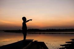 Schattenbild des Jungen stehen oben Blick der Sonnenuntergang auf dem Boot Stockfotografie