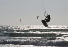 Schattenbild des junger Mann-Drachen-Einstiegs im Meer bewegt wellenartig Lizenzfreies Stockfoto