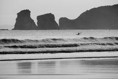 Schattenbild des Kanufahrerrudersports und -fischens in Atlantik durch deux jumeaux im Sonnenaufgang in Schwarzweiss Stockfotografie