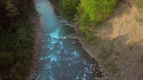Schattenbild des kauernden Geschäftsmannes Fliegen über den schönen Gebirgsfluss und schönen den Waldluftbildkameraschuß Majestät stock footage