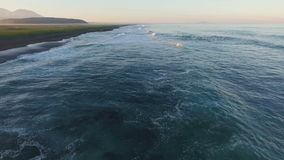Schattenbild des kauernden Geschäftsmannes Fliegen entlang das Ufer des Ozeans stock video