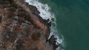 Schattenbild des kauernden Geschäftsmannes Wellen, die gegen Felsen abbrechen Meereswellen auf gefährlichen Felsen von einer Pano stock video footage