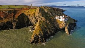 Schattenbild des kauernden Geschäftsmannes Wicklow-Kopfleuchtturm Grafschaft Wicklow irland Lizenzfreie Stockbilder