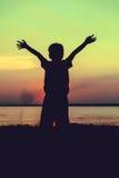 Schattenbild des Kindes die Ansicht am Flussufer genießend Quer-proces Stockfotos