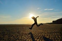 Schattenbild des Kindes laufend auf Strand Stockbild