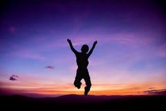 Schattenbild des Kindes oben springend Lizenzfreie Stockbilder