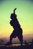 Schattenbild des Kindes springend gegen Sonnenuntergang Junge, der das Konkurrierung genießt Lizenzfreies Stockbild