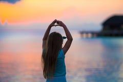Schattenbild des kleinen Mädchens Herz bei Sonnenuntergang auf dem Strand machend Lizenzfreies Stockfoto