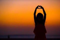 Schattenbild des kleinen Mädchens Herz bei Sonnenuntergang auf dem Strand machend Stockbilder