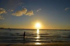 Schattenbild des kleinen Mädchens schlendernd in den Strand in Richtung zum Sonnenuntergang Lizenzfreies Stockbild