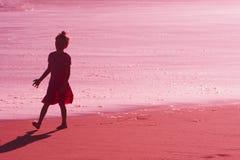 Schattenbild des kleinen Mädchens am Sonnenuntergang auf Strand Stockfotos