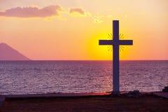 Schattenbild des Kreuzes bei Sonnenaufgang oder des Sonnenuntergangs mit hellen Strahlen und Seepanorama Lizenzfreie Stockfotos
