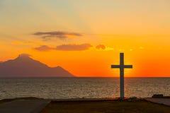Schattenbild des Kreuzes bei Sonnenaufgang oder des Sonnenuntergangs mit hellen Strahlen und Seepanorama Stockfotografie