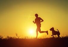 Schattenbild des Läufers mit Hund im Sonnenuntergangaufstieg Stockfoto