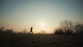 Schattenbild des laufenden Mannes am Morgen gegen den Sonnenaufgangsonnenuntergang stock footage