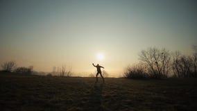 Schattenbild des lustigen verrückten Manntanzens gegen Sonnenaufgang oder Sonnenuntergang Erfolgreiches frohes und nettes Manntan stock footage