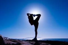 Schattenbild des Mädchens Übungen an der Küste tuend Lizenzfreie Stockfotos