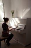 Schattenbild des Mädchens, das das weiße Klavier spielt lizenzfreie stockfotos